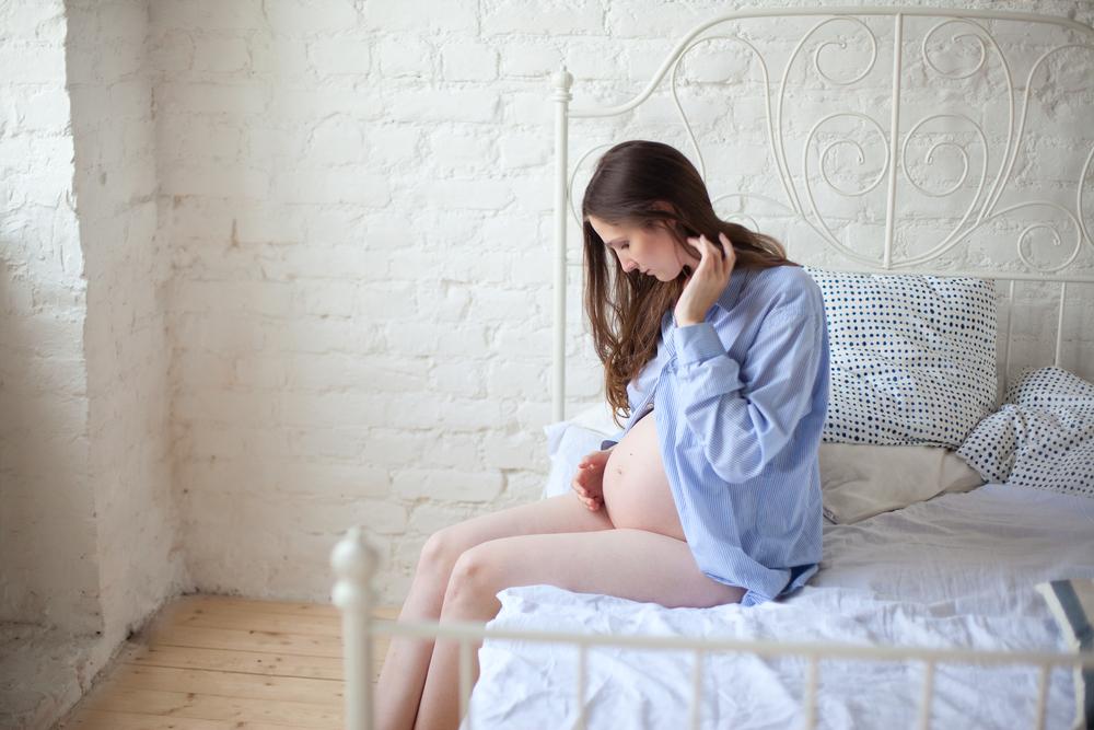 Mentale Einflussfaktoren: Schwangere Frau spricht zu Baby